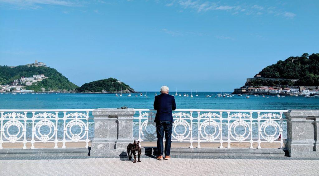 Un hombre mira al mar junto a su perro